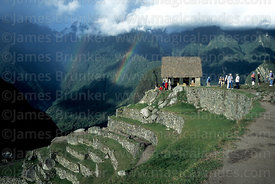 Tourists next to the Watchmans Hut, rainbow over Urubamba canyon, Machu Picchu, Peru