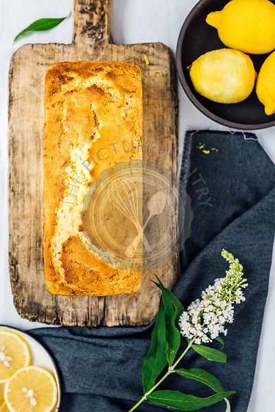 Lemon zucchini bread on a wooden board is photographed from top view. Lemons, lemon slices and a flower accompany this.