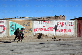 Women walking past propaganda showing support for Evo Morales and the industrialisation of the Salar de Uyuni's lithium reserves, Colchani, Bolivia
