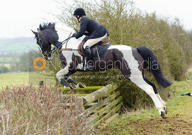 Hilary Butler jumps a hedge away from the meet at Ladywood Lodge