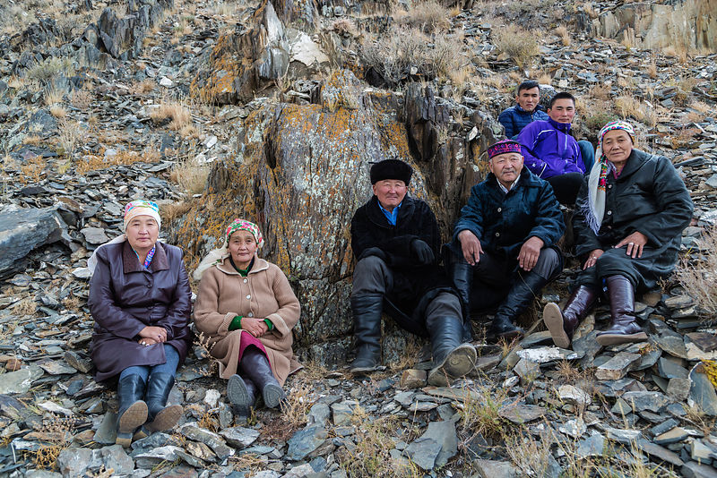 Kazakh Family Watching Festival Event from the Side of a Hill