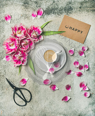 Flat-lay of cup of coffee surrounded with pink tulip flowers and sign happy over grey marble background