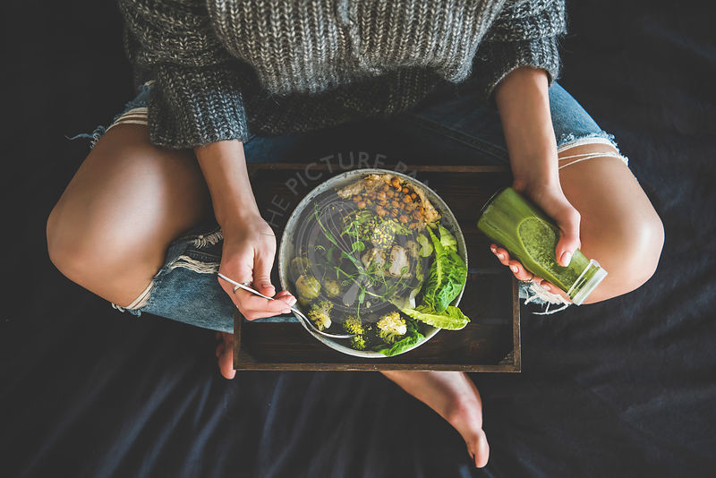 Woman in bed eating vegan dish and drinking smoothie