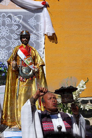 Priest holding incense burner aloft during mass for San Bartolome at start of Chutillos festival, Potosí, Bolivia