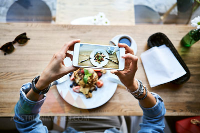 Overhead view of woman taking smartphone picture of pancakes in cafe