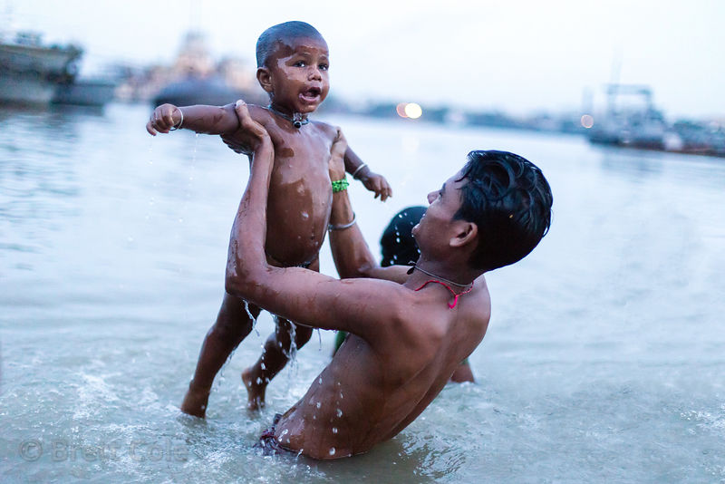Father and son in the Hooghly River during Mahalaya, Babughat, Kolkata, India