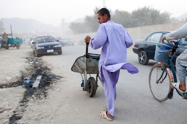 Bashir 13 ans pousse sa brouette dans une rue de Kaboul, Afghanistan / Bashir 13 years-old pushing his wheelbarrow in a street of Kabul, Afghanistan