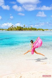 Beautiful woman jumping on beach, Tikehau, French Polynesia