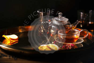 Small glass teapot with hot black tea, glasses and golden tray
