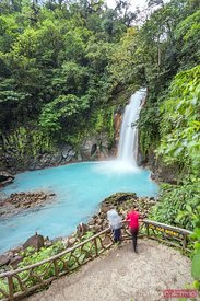 Tourist couple looking at Rio Celeste waterfall, Costa Rica
