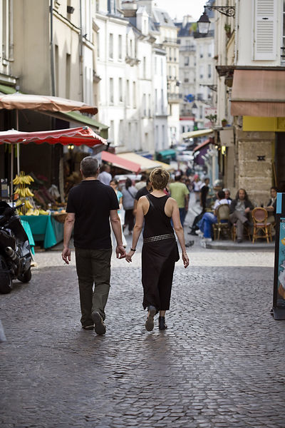 France - Paris - A couple touch fingers as they stroll through the market on the Rue Mouffetard.