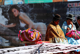 Aymara women in front of a Cuba Libre hoarding watch the Gran Poder festival, La Paz, Bolivia