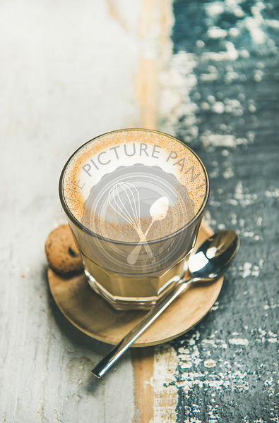 Classic foamy cappuccino coffee in glass over wooden background