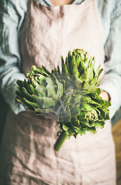 Female farmer in apron holding fresh artichokes