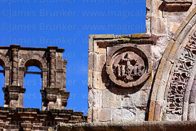 Detail of christogram carving on entrance archway of Nuestra Señora de la Asunción church, belfry in background, Juli, Puno Region, Peru