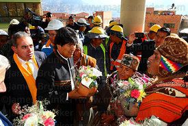 Bolivian president Evo Morales (centre) receives a ceramic pot with offerings from an Aymara amauta or shaman during the opening ceremony of the Yellow Line cable car, La Paz, Bolivia