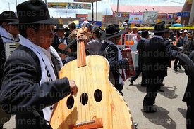 Musician playing acoustic bass guitar, Virgen de la Candelaria festival, Puno, Peru