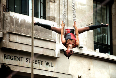 Woman with Painted Face Upside down on a Trapeze in Regent Street London