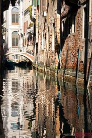 Typical canal in Venice, with brick houses reflected in the water