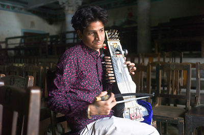 India - Chandannagar - Umesh Mishra, 26 a sarangi virtuoso tunes his instrument before a concert later that night at the Nrityagopal Smriti Mandir, a concert hall in