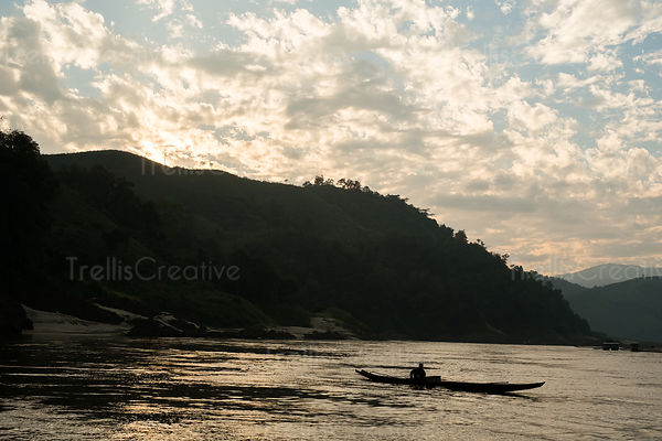 Silhouette of a person travelling in boat on the Mekong river