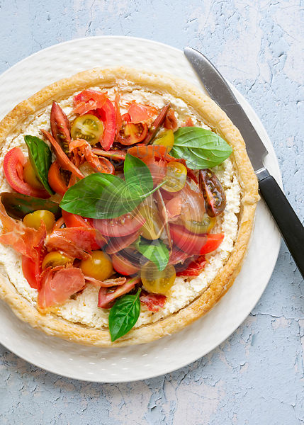 Round savoury tart filled with feta cheese, pancetta, tomatoes and basil leaves on a plate with a knife.