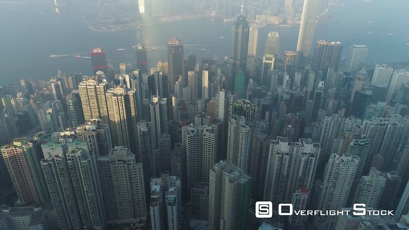 Hong Kong Skyline and Victoria Harbour. Aerial View. Drone is Flying Sideways and Ascending. Camera is Tilting Up. Reveal Shot.