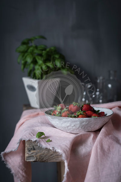 Fresh strawberries in a bowl in a rustic kitchen