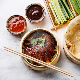 Sliced Peking Duck in bamboo steamer served with fresh cucumber, green onions, cilantro and roasted wheaten chinese pancakes with sauce Hoysin on white background close-up