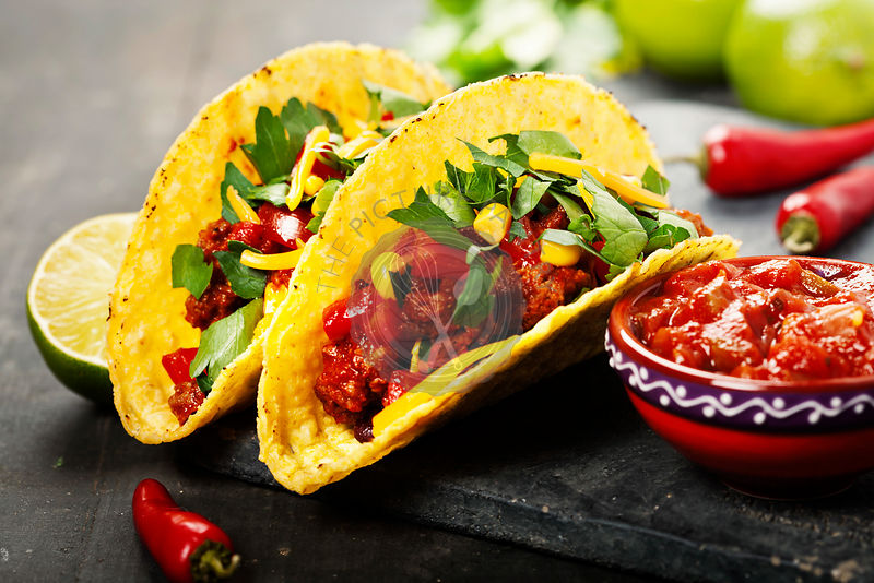 Mexican tacos with meat, beans and salsa on rustic background