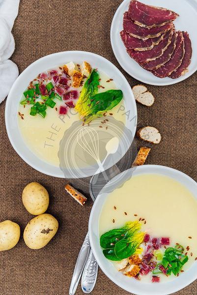 Cream of potato soup topped with green onions, spinach, simit croutons, flax seeds and aged beef in two white bowls photographed from top view. Aged beef, baby potatoes and croutons accompany.