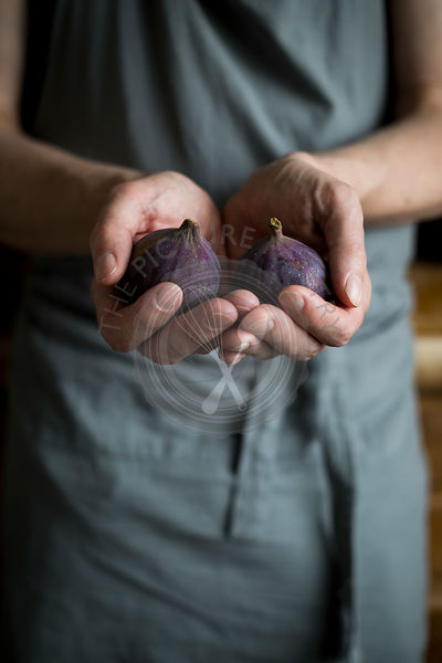 Man with kitchen apron holding figs in his hands