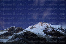 Stars above Mt Huayna Potosí and lights of climbers on glacier ascending peak, Cordillera Real, Bolivia