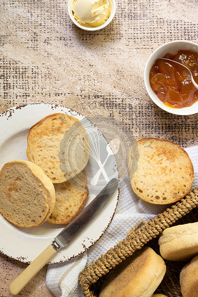 English muffins on a plate with a bowl of apricot jam, butter and a knife.