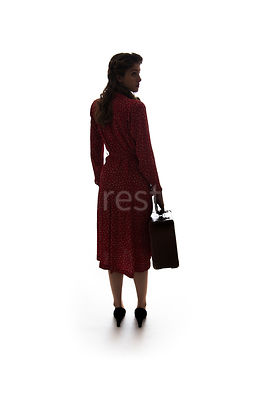 A silhouette of a 1940's woman in a red dress, walking away with a suitcase – shot from eye-level.