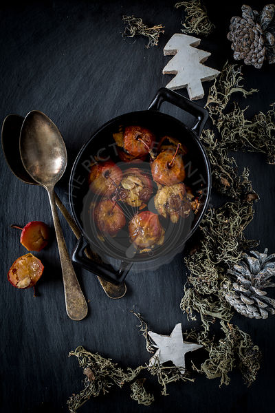 Stuffed roast apples in cocotte on slate background with spoons and Christmas decoration.Top view