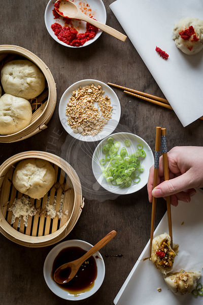 Woman's hand with chopsticks placing stuffed dumpling on sandwich paper over wooden tabletop with bamboo steamers. Top view