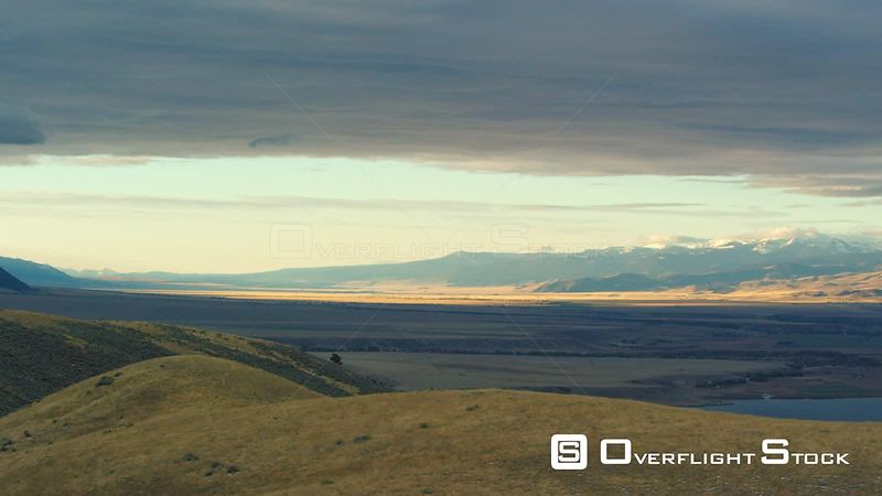 The dawn sun highlights the golden autumn colors of the Madison Valley in Southwestern Montana, as the Gravelly mountain range rises in the distance