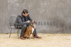 boxer dog with man in suit sitting on wire chair