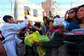 Priest blessing miniatures with holy water outside church at Alasitas festival, Puno, Peru