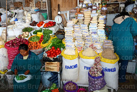 Woman selling fresh vegetables and a variety of flours on stall in San Pedro market, Cusco, Peru
