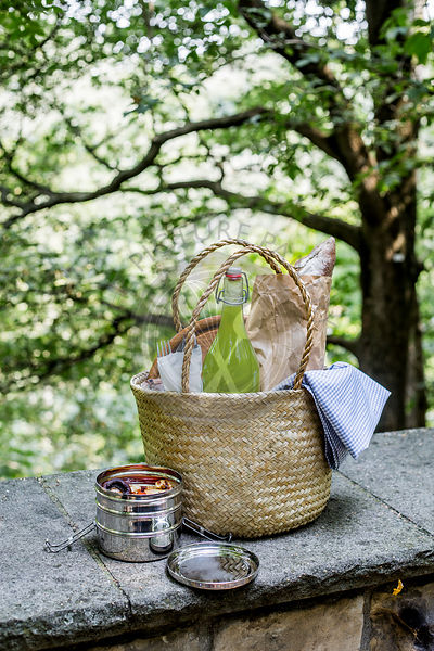 Picnic basket on wall with lemonade bottle, lunch box, artisan bread in a paper bag, and picnic blanket