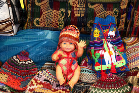 White plastic doll wearing woolly hat on stall in Pisac market, Sacred Valley, Peru