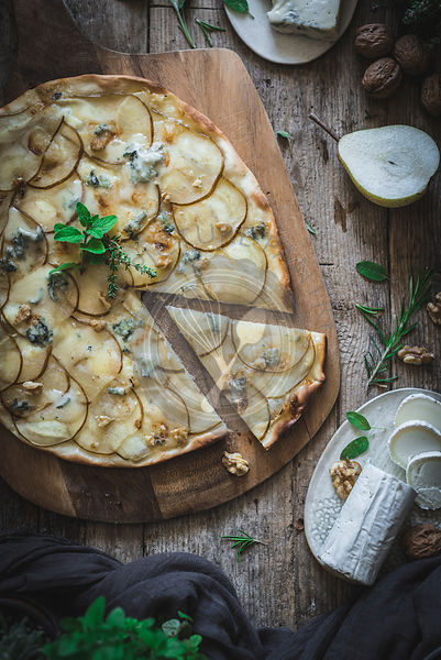 Pear and Gorgonzola homemade Pizza on a rustic wooden background
