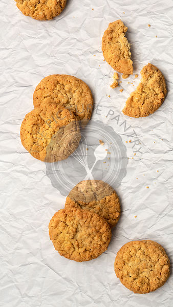 Honey and oatmeal biscuits with a two broken halves on a textured paper background.