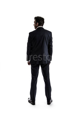 A mystery man in a suit, standing, in semi-silhouette – shot from eye level.