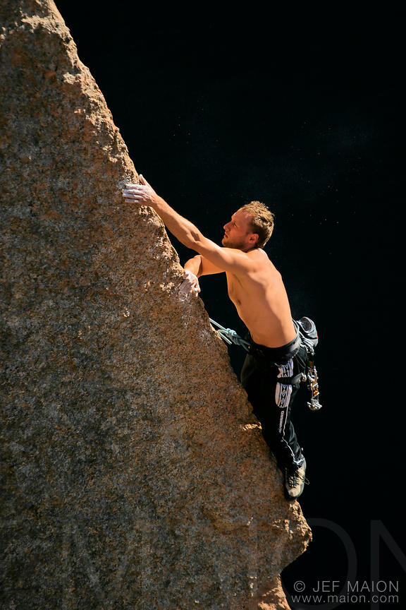 Bare chest rock climber in warm evening light