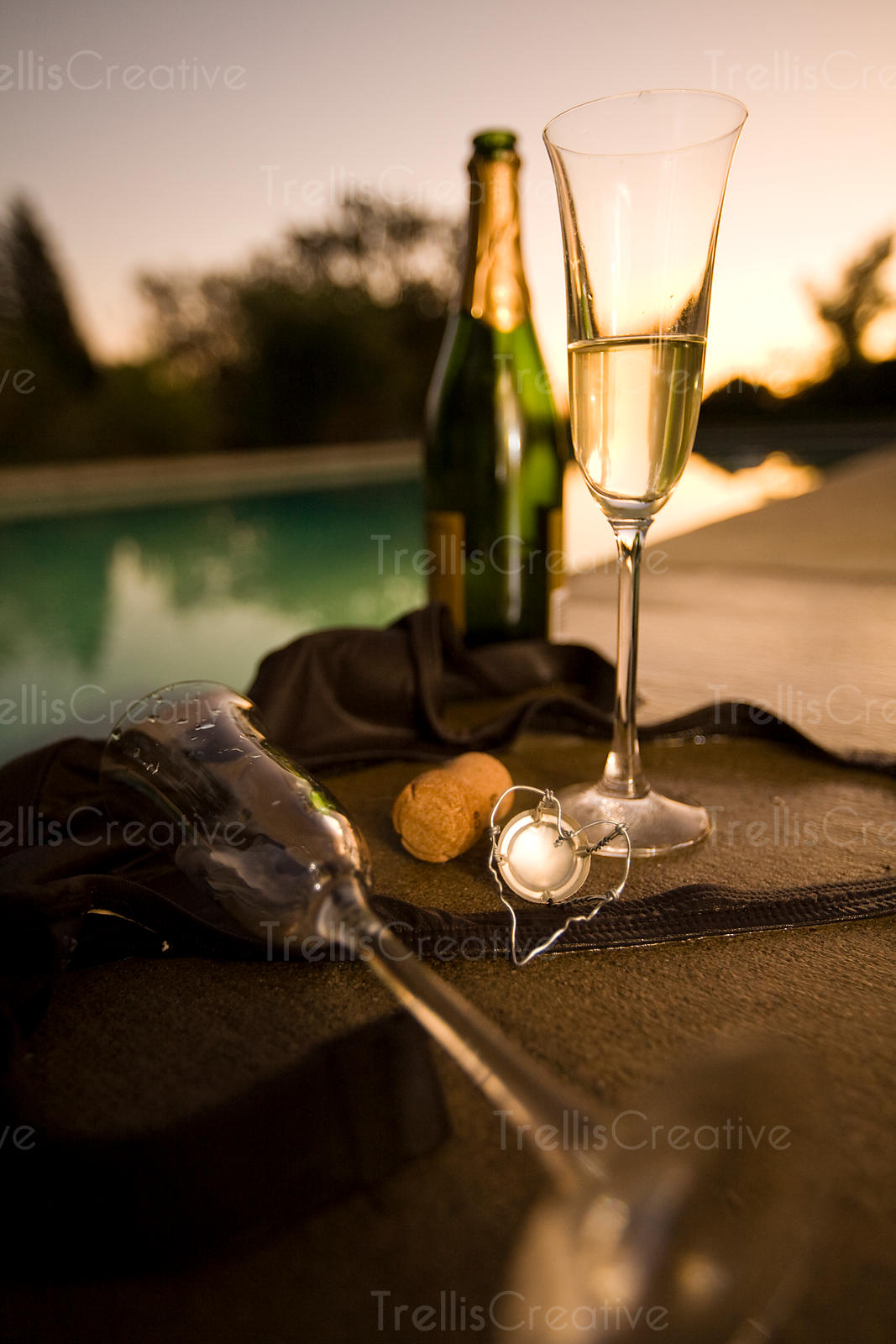A woman's bikini top, two empty glasses and a bottle of champagne poolside