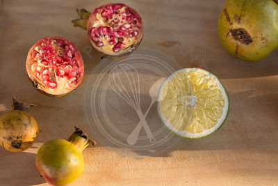 cut pomegranates in late afternoon sun with lemon against pale wood background