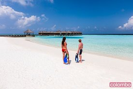 Couple with snorkeling gear on a beach, Maldives